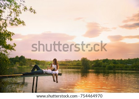 Beautiful bright fairy walk of a loving couple in the summer at sunset. A guy in a white shirt and jeans with a girl in a sarafan embraces, dancing, sitting on the pier. Pond in the background. Place #754464970