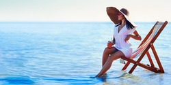 Beautiful caucasian girl in sunhat and white tunic sitting on the beach chair at seaside while holds cocktail. Looking in sideways. Summer vacation. Skin care