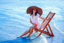 Beautiful caucasian girl in sunhat and white tunic sitting on the beach chair at seaside while holds cocktail. Loking in sideways. Summer vacation. Skin care