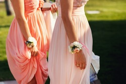 Beautiful elegant slim bridesmaids in delicate pink beige summer dress with bracelets of the luxury fresh roses on the wedding ceremony