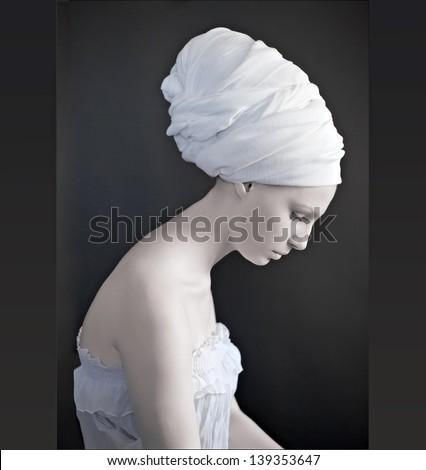 beautiful female model looking as marble statue, wearing head wrap