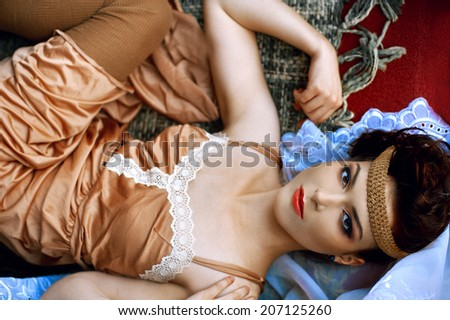 Beautiful girl in retro style is lying on the shits wearing an old-style nightgown
