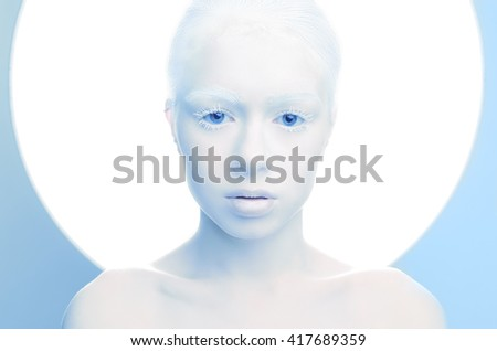 Shutterstock  beautiful girl with white skin, lips and white hair albino. Photo face on a blue background portrait of the head and behind plate