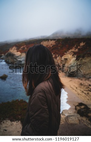 beautiful girl woman being introspective along the coastline past Monterey California and Carmel by the sea in a foggy and serene peace by the ocean thinking about what is next and existence