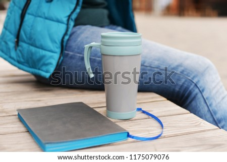 beautiful girl young student businessman sitting outdoors in park outdoors in winter autumn with a king with a cup of coffee or tea #1175079076