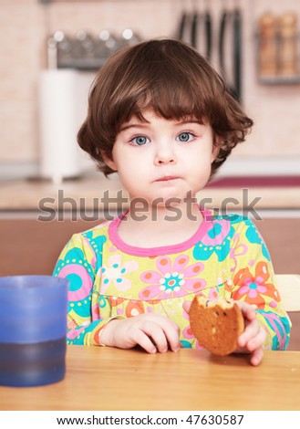 beautiful little girl eating in the kitchen