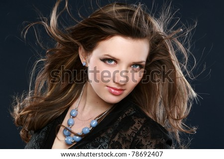 Beautiful long haired brunette. Studio portrait on dark-blue background