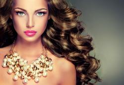 Beautiful model brunette with long curled hair . Girl with big necklace with beads and chain . Jewelry and accessories .Hairstyle wavy curls . Makeup color fuchsia .