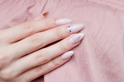 Beautiful pink manicure with a trendy design on a pink background