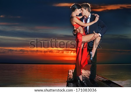 Beautiful romantic couple in tango pose against sunset background