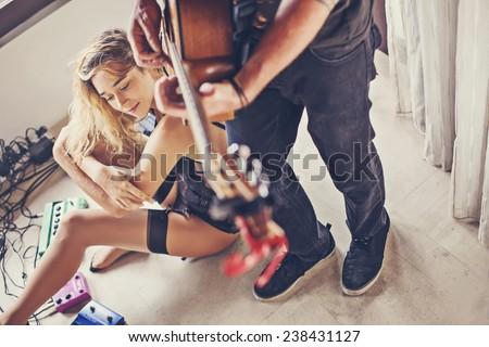 beautiful sexy girl and her boyfriend playing guitar