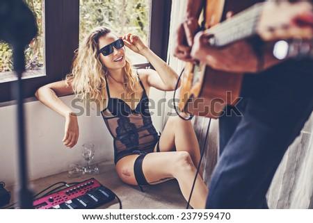 beautiful sexy girl watching her boyfriend playing guitar  (\