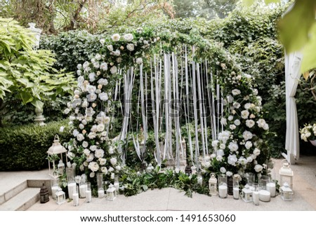 Beautiful wedding set up. Area of the wedding ceremony. Round arch, white chairs decorated with flowers, greenery. Cute, trendy rustic decor.festive decor, flower #1491653060