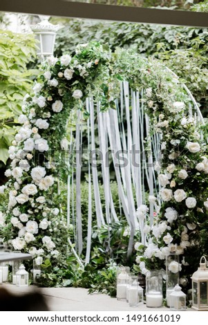 Beautiful wedding set up. Area of the wedding ceremony. Round arch, white chairs decorated with flowers, greenery. Cute, trendy rustic decor.festive decor, flower