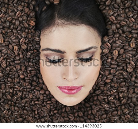 Beautiful woman face in coffee beans