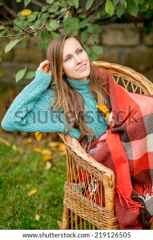 Beautiful woman in the garden wrapped in a plaid blanket sitting in armchair. Sweater autumn woman