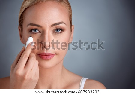 beautiful woman putting concealer under her eyes #607983293