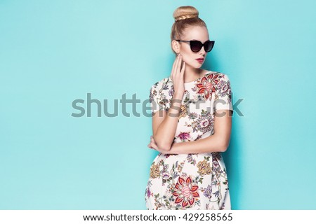 beautiful young blonde woman in nice spring dress, elegant black sunglasses posing in a studio. Fashion spring summer photo