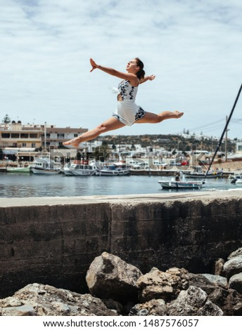 Beautiful young fit gymnast woman performing art gymnastics element, jumping, doing split leap dancing against the background of a Greek town with a pier with boats
