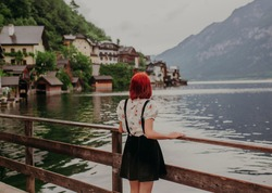 Beautiful young girl enjoying view of lake and mountains of  Fairy tale village Hallstatt.