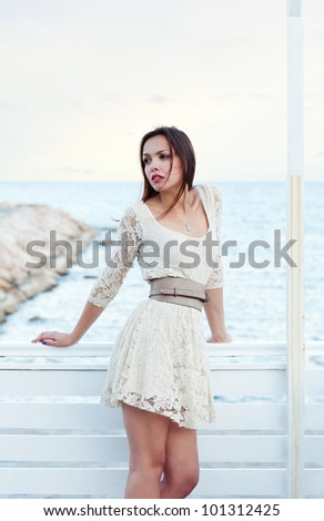 beautiful young girl in a short beige lace dress outside.