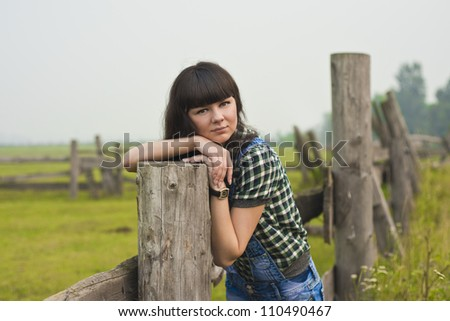 beautiful young girl posed near a fence in the field