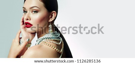 Beautiful young girl with bright lips in studio at half a turn. Jewelry pearl jewelry - earrings, bracelet, necklace.Fashion, beauty, jewelry, pearls, jewelry, earrings, necklaces, bracelets, boutiqu