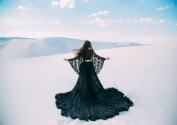 Beauty a woman, rear view. Queen in black clothes stands in desert. Girl fashion model. long silk dress with a train. Back of luxury elegant goddess. backdrop a white sand, blue sky. Silhouette photo