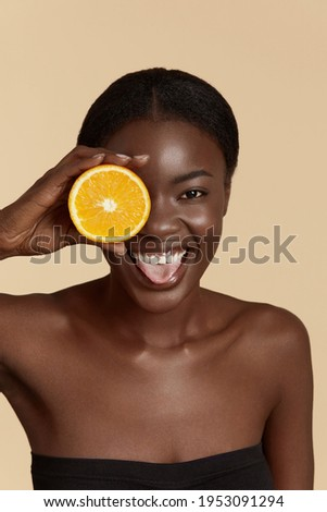Beauty. Black woman with healthy face skin squeezing orange in hand. Beautiful smiling girl model with natural makeup, glowing facial skin and citrus fruit. Vitamin C cosmetics concept Zdjęcia stock ©