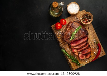 Beef steak, herbs and spices on a cutting board on a background of stone, top view copy space for your text