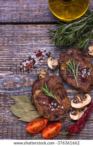 Beef Steak, olive oil, salt, pepper, tomatoes, rosemary  on the wooden board, background. #376361662