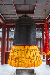 Bell covered with the Confucius wisdom how to rule the country. Nanjing Confucius Temple. Nanjing, China. On the yellow strips: