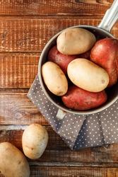 Belyy    kartofel' na starom  vintazhnom derevyannom fone iz dosok. Rezannyy kartofel'. Vid sverkhu. Natyurmort s kartofelem. Produktovyye ingrediyenty.      Kartofel' na meshkovine, tkanevom meshke.