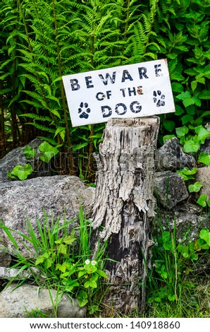 'Beware if the Dog' sign mounted on a tree stump with green foliage behind - stock photo