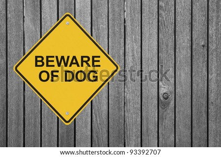 """Beware of Dog"" sign on a wooden fence"