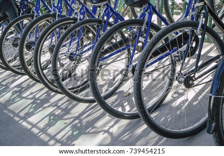 bicycle rent Public bicycles, sharing bikes saddle. Detail view of a bike wheel with more bicycles lined up. Bicycle rent. Closeup of bicycle wheels #739454215