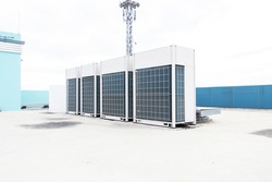 Big air conditioner compressor source heat pumps on the wall outdoor on the roof top of the building. It is used in large industrial buildings for cooling. with sky and spotlights in the background.