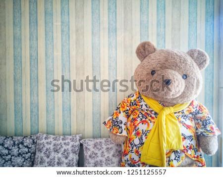 ิฺBig teddy bear in living room with pastel background patterns vintage wallpaper and cute pillow.