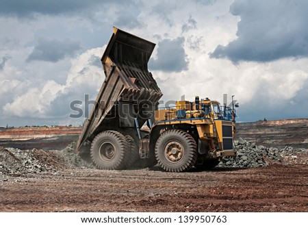 big yellow mining truck unload iron ore