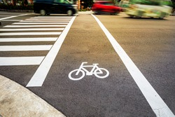 Bike lane with white bicycle sign beside crosswalk on city street and blur moving car on the background, road safety and alternative way of transportation concept