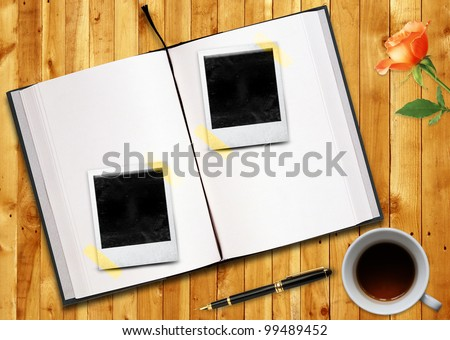 Biography or curriculum vitae Conceptual image, blank opened book outdoors on wooden disk Pen, blank photo frame and cup of tea.