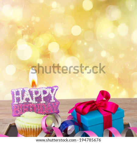 birthday cupcake with burning happy birthday candle on golden background with copy space