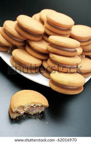 Biscuits. Sweet sandwich-biscuits filled with hazelnut cream arranged in a pyramid on a white plate with one bitten on dark background