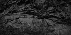 Black and white background. Volumetric black stone background. 3d effect. Rock texture. Granite mountain texture. Close-up.