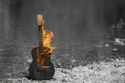 black and white image, the main object is painted in orange. wooden guitar burns, outdoors, near the river
