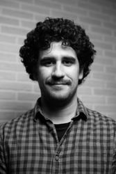Black and white monochrome portrait of a red curly haired man with a mustache who looks like the scientist Einstein.