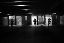 black and white photography.  Cyclist rides in a pedestrian crossing, silhouette and reflection in the wall