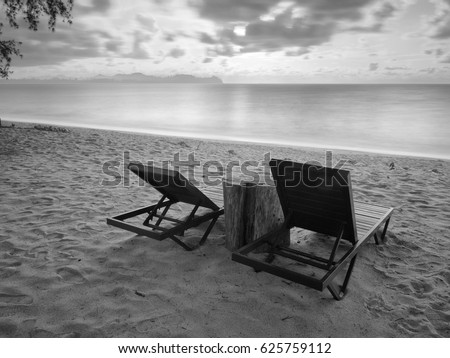 Black and white photography of  rest bench on a beach with cloudy sky