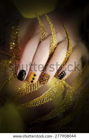 Black and yellow manicure with different colors of nail Polish and rhinestones of different shapes.