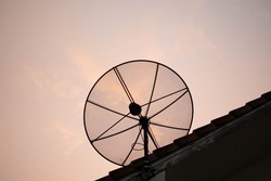 Black antenna satellite dish over the sunset sky in Thailand.